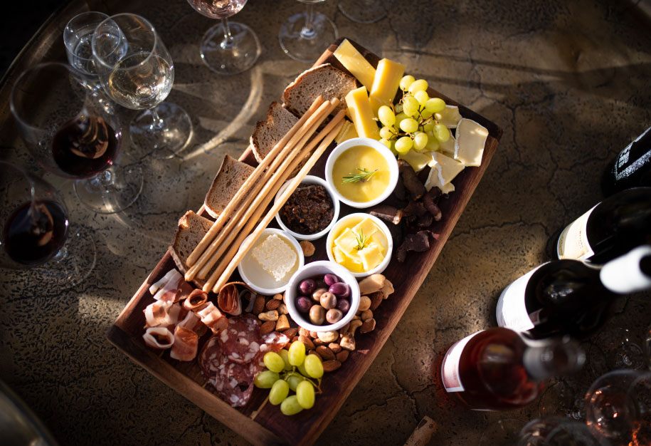 a range of paserene wine bottles and glasses with a top down view of the charcuterie food platter displayed at the top wine tasting near franschhoek in cape town