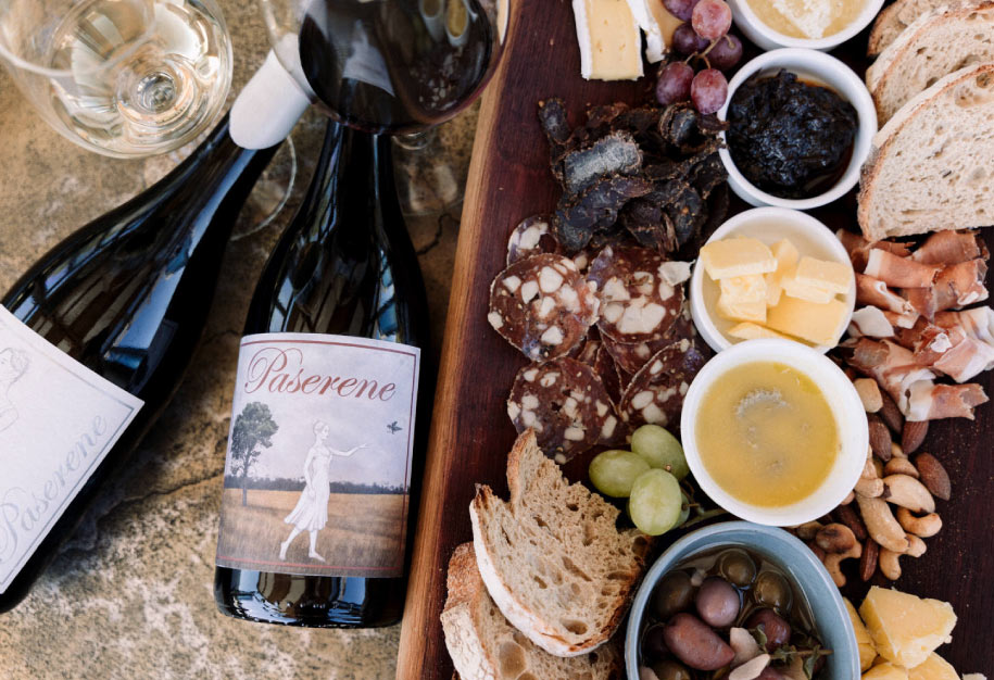 a range of paserene wine bottles and charcuterie food platter displayed at the top wine tasting near franschhoek in cape town